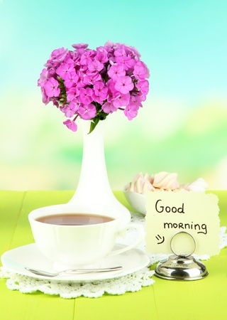 Beautiful bouquet of phlox with cup of tea on table on light background photo