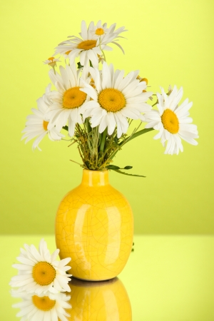 Beautiful bouquet chamomiles in vase on color background Stock Photo - 21254991