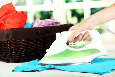 Womans hand ironing clothes, on bright background photo