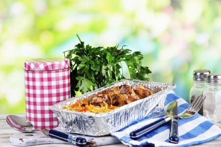 Food in boxes of foil on napkin on wooden board on wooden table on nature background photo