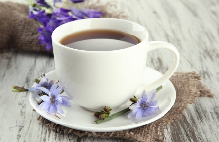Cup of tea with chicory, on wooden background photo
