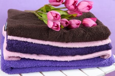 Towels and flowers on wooden chair on purple background photo