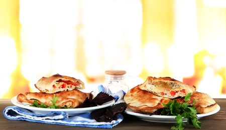 Pizza calzones on plates on table on room background photo