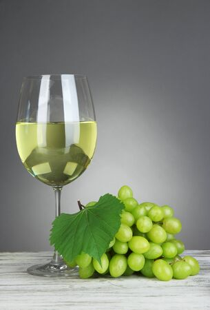 Ripe delicious grapes with glass of wine on table on gray background photo