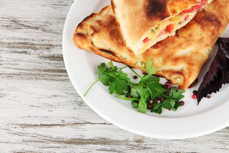Pizza calzones on plate on wooden table photo