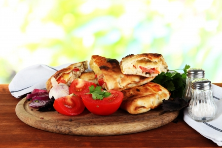 Pizza calzones on wooden board near napkin on wooden table on nature background photo