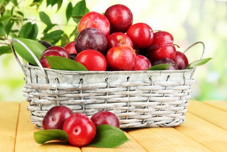 Ripe plums in basket on wooden table on natural background photo