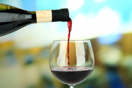 Red wine being poured into wine glass, on bright background photo