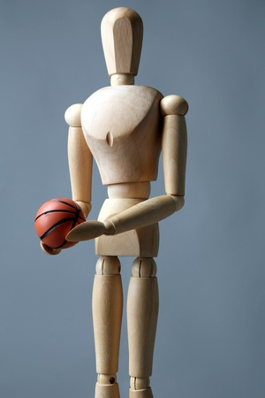 Wooden mannequin with basketball ball on grey background photo