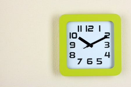 Office clock on color wall background photo
