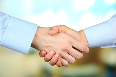 Business handshake on bright background photo