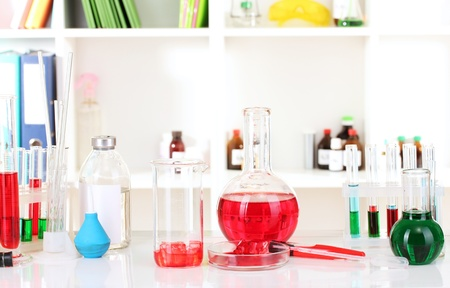 Different laboratory glassware with color liquid on laboratory background photo