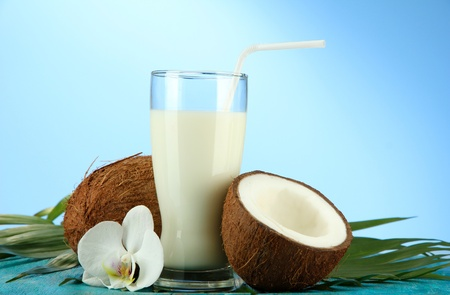 Coconuts with glass of milk,  on blue background photo