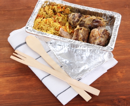 Food in box of foil on napkin on wooden background photo