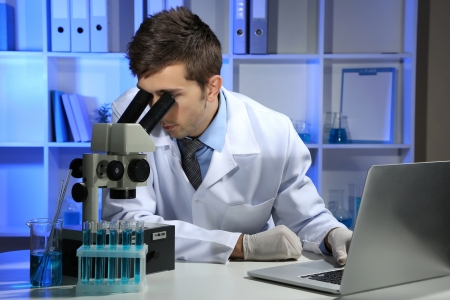 Young laboratory scientist  looking at microscope in lab Stock Photo