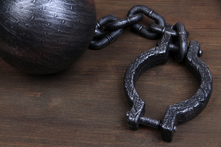 cuff bracelet: Ball and chain on wooden background Stock Photo