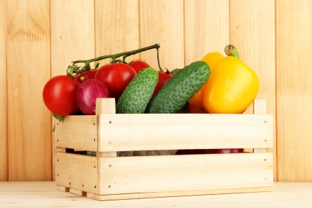 Fresh vegetables in box on wooden background photo