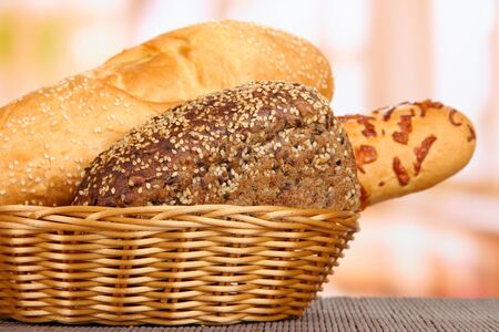 Baked bread in wicker basket on window background photo