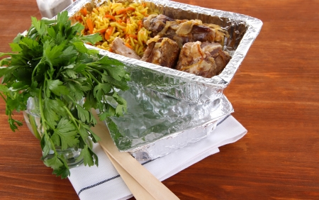 Food in boxes of foil on wooden background photo