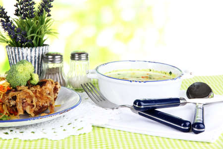 Soup and rice with meat in plates on napkin on tablecloth on nature background photo