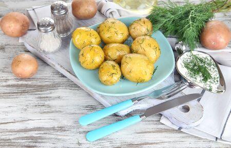 platen: Boiled potatoes on platen on wooden board near napkin on wooden table