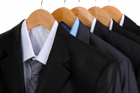 Suits with shirts on hangers on white background photo