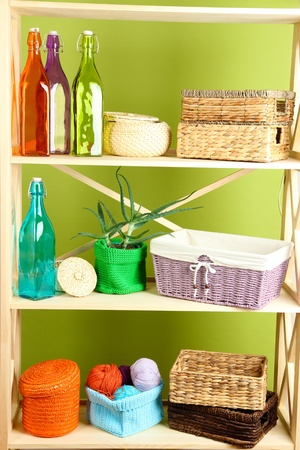 Beautiful white shelves with different home related objects, on color wall background Stock Photo - 21312682