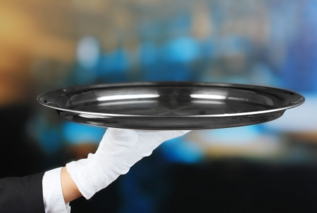Empty tray in hand waiter on restaurant background photo
