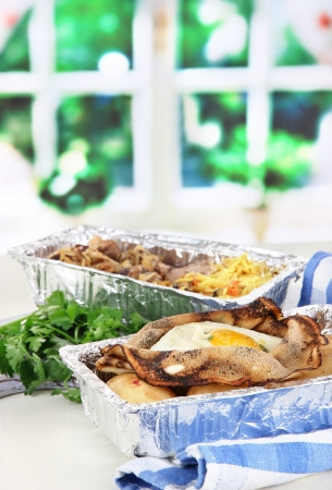 Food in boxes of foil on napkin on wooden board on window background photo