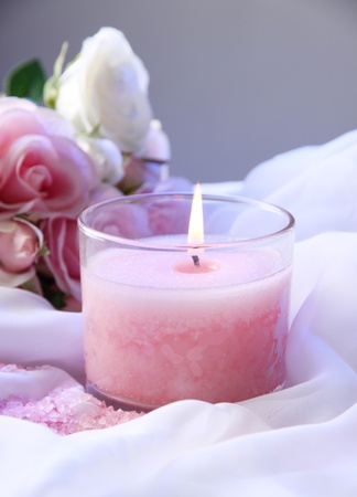Beautiful candle with flower on white cloth, close up photo