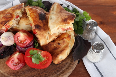 Pizza calzones on wooden board near napkin on wooden table photo