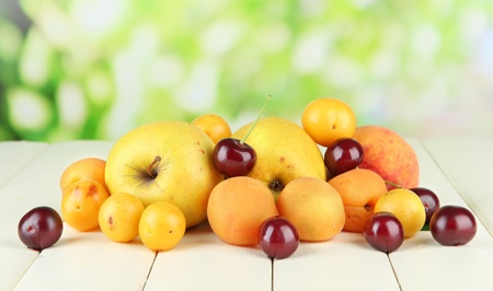 fructose: Bright summer fruits on wooden table on natural background