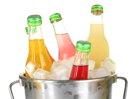 Bottles with tasty drinks in bucket with ice cubes, isolated on white photo