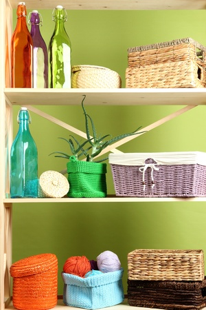Beautiful white shelves with different home related objects, on color wall background Stock Photo - 21335780