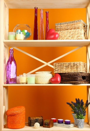 Beautiful white shelves with different home related objects, on color wall background Stock Photo - 21335342
