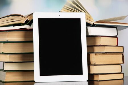 Tablet and books on light background photo