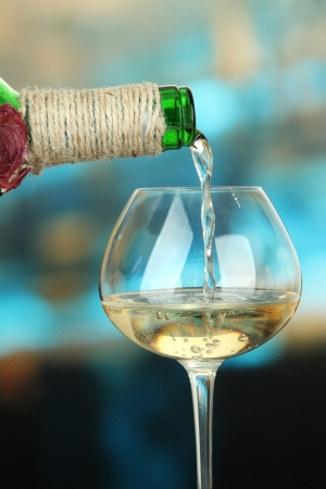 White wine being poured into wine glass, on bright background photo