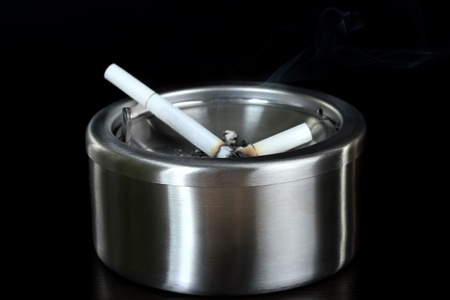 Metal  ashtray with cigarette, isolated on black photo