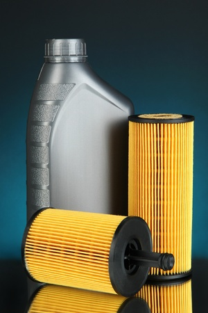 Car oil filters and motor oil can on dark color background photo
