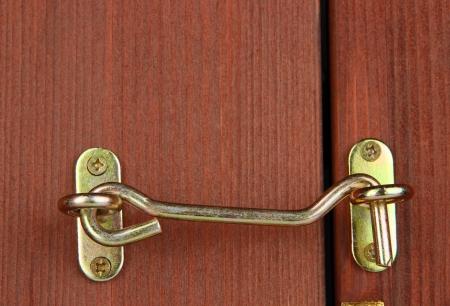 pawl: Metal hook in wooden door close-up
