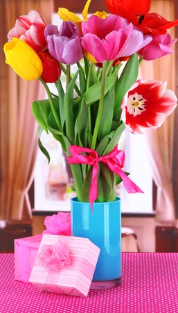 bow window: Beautiful tulips in bouquet with gifts on table in room