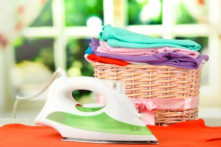 Steam iron and wicker basket with clothes, on bright background photo