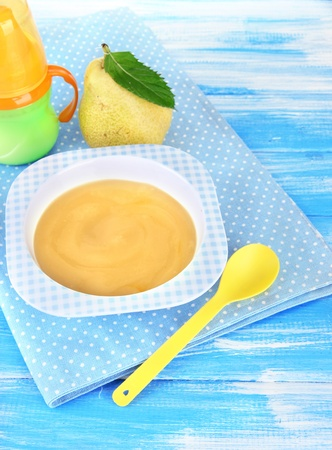 Tasty baby fruit puree and baby bottle on wooden table Stock Photo - 21337671