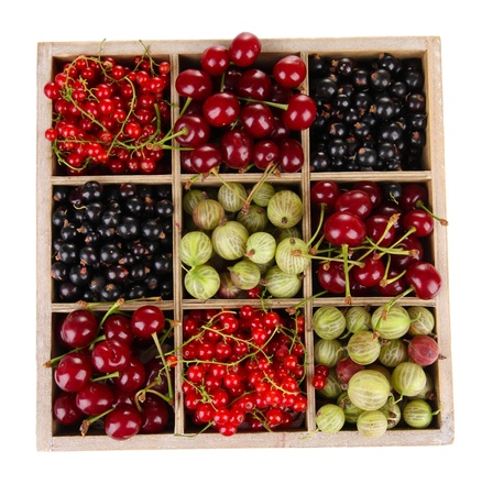 berry fruit: Different summer berries in wooden crate isolated on white Stock Photo