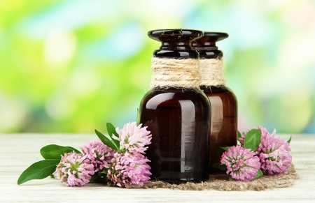 Medicine bottles with clover flowers on wooden table, outdoors photo