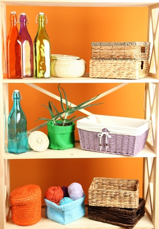 Beautiful white shelves with different home related objects, on color wall background Stock Photo - 21337762