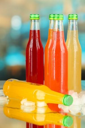 Botellas con sabrosas bebidas con cubitos de hielo, en el fondo brillante Foto de archivo