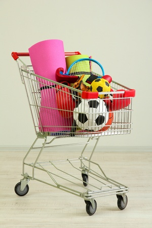 karemat: Shopping cart with sport equipment, on gray background Stock Photo