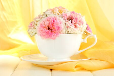 Roses in cup on wooden table on yellow cloth background photo