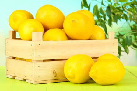 Ripe lemons in wooden box on table on bright background photo